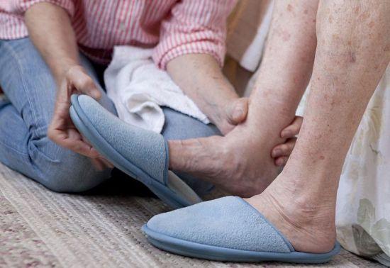 Бабушке одевают тапочки на ноги