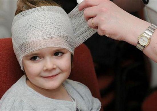 Ребенку забинтовывают голову