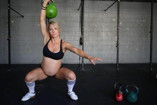 Беременная поднимает гирю